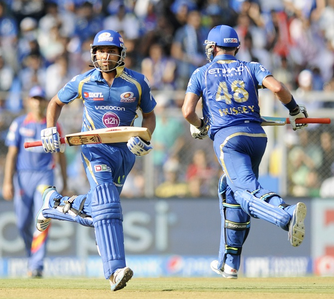 Mumbai Indians captain Rohit Sharma and Michael Hussey run between the wickets.