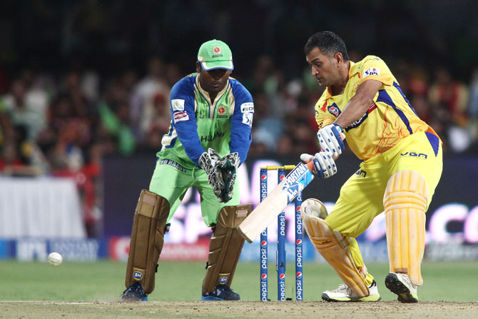Chennai captain MS Dhoni plays a shot as RCB's Yogesh Takawale looks on