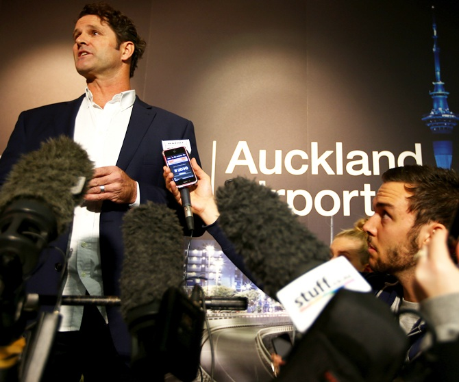 Chris Cairns reads a prepared statement to the media at a press conference at Auckland Airport.