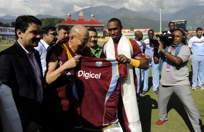 His Holiness the 14th Dalai Lama is presented with a West Indies team jersey by Dwayne Bravo captain of West Indies before the start of the 4th One Day International in Dharamsala in October 2014