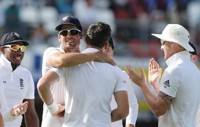 England's James Anderson celebrates with Alastair Cook after taking the wicket of West Indies' Denesh Ramdin, to  break the Ian Botham's record for most Test wickets by an England player