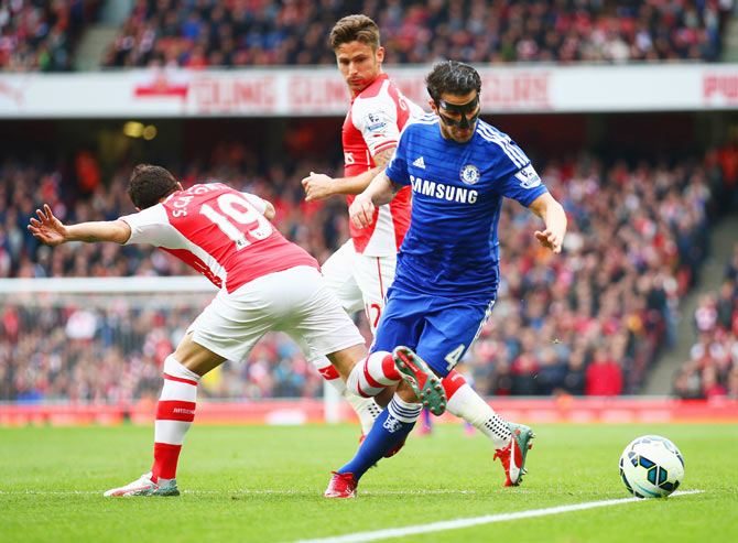 Chelsea's Cesc Fabregas is challenged by Arsenal's Santi Cazorla and Olivier Giroud