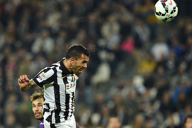 Carlos Tevez of Juventus FC heads to score during their Serie A match against ACF Fiorentina at Juventus Arena in Turin on Wednesday
