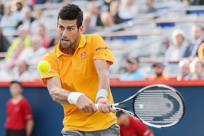 Serbia's Novak Djokovic plays a return against Brazil's Thomaz Bellucci during their 2nd round match of the Rogers Cup at Uniprix Stadium in Montreal, Canada, on Tuesday
