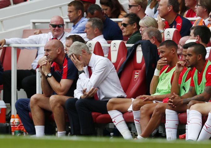 Arsenal manager Arsene Wenger looks dejected as assistant manager Steve Bould looks on during their season-opening loss against West Ham