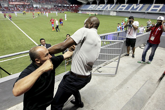 Costa Rica coach Paulo Wanchope (right) fights with a security guard during the Olympic qualifying match between Costa Rica amd Panama at the Maracana stadium in Panama City on Tuesday, August 11