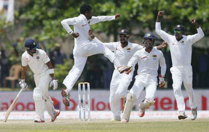 Sri Lanka's Tharindu Kaushal (second from left) celebrates with his teammates after taking the wicket of India's Virat Kohli (left) during Day 4 of the first Test match in Galle on Saturday, August 15
