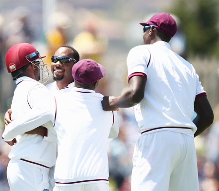 West Indies's Jomel Warrican celebrates dismissing Australia's David Warner during Day 1 of the first Test at Hobart