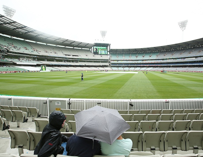 Fans wait as rain delays play during day four of the Third Test match between Australia and India at   Melbourne Cricket Ground on December 29, 2014 in Melbourne