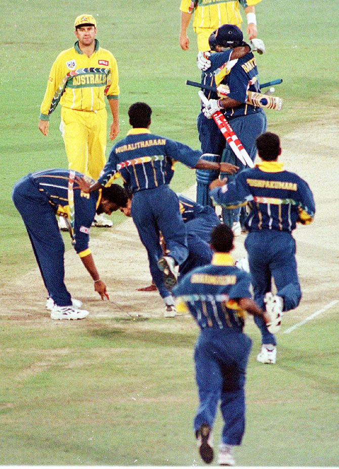 Sri Lankan team members rush onto the wicket to celebrate with batsmen Arjuna Ranatunga and Aravinda De Silva (hugging) after they beat Australia to win the World Cup at the Gaddafi stadium in Lahore on March 17, 1996