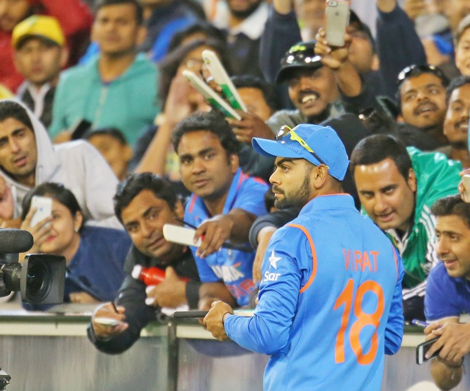 Virat Kohli of India signs autographs