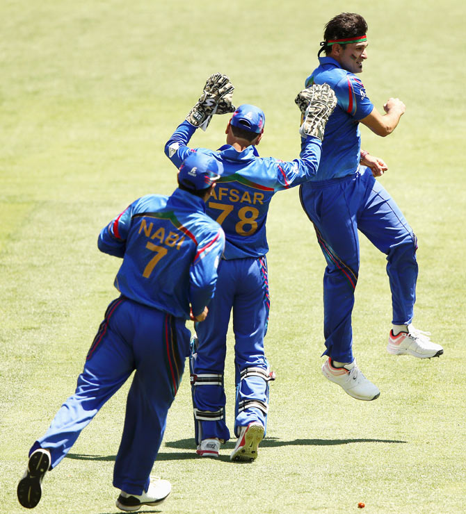 Hamid Hassan of Afghanistan celebtrates after bowling out Shikhar Dhawan of India during their 2015 ICC Cricket World Cup warm up match at Adelaide Oval on Tuesday