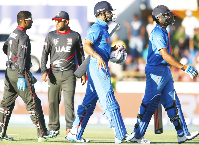 Virat Kohli, second from right, and Rohit Sharma walk off the field during a break in play against the UAE. David Gray/Reuters