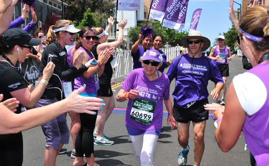 Harriete Thomson crosses the finish line amidst cheers as she completes the San Diego marathon on Sunday