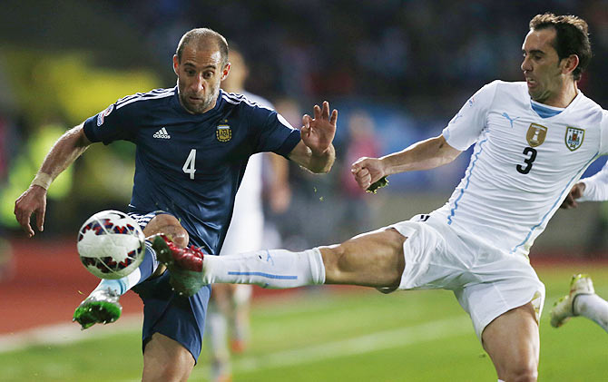 Argentina's Pablo Zabaleta is tackled by Uruguay's Diego Godin (right)
