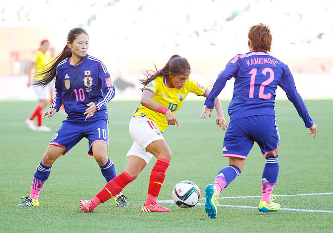 Kerlly Real #19 of Ecuador controls the ball against Homare Sawa #10 and Megumi Kamionobe #12 of Japan