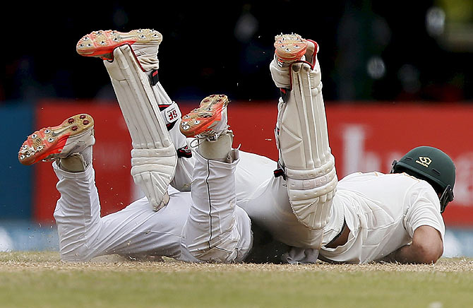 Pakistan's Ahmed Shehzad (top) collides with Sri Lanka's Kaushal Silva as he tries to make his ground on the third day of their second Test in Colombo on June 27