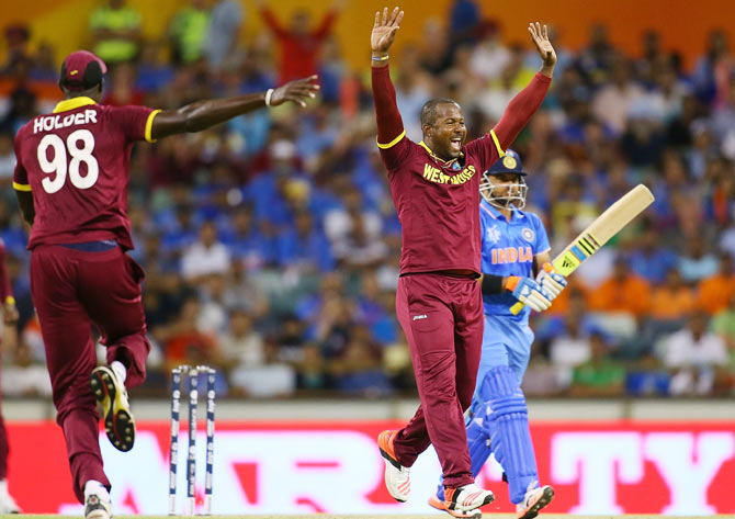 West Indies' Dwayne Smith celebrates the wicket of India's Suresh Raina during their World Cup match at the WACA in Perth on Friday