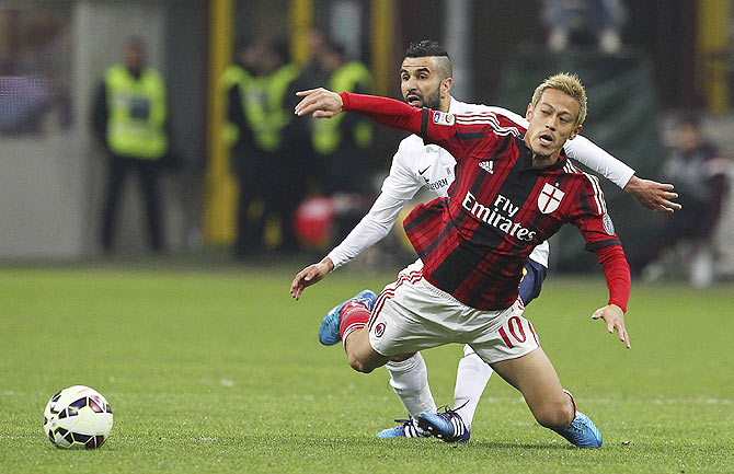 Keisuke Honda of AC Milan is challenged by Mounir Obbadi of Hellas Verona FC during the Serie A match at Stadio Giuseppe Meazza in Milan on Saturday