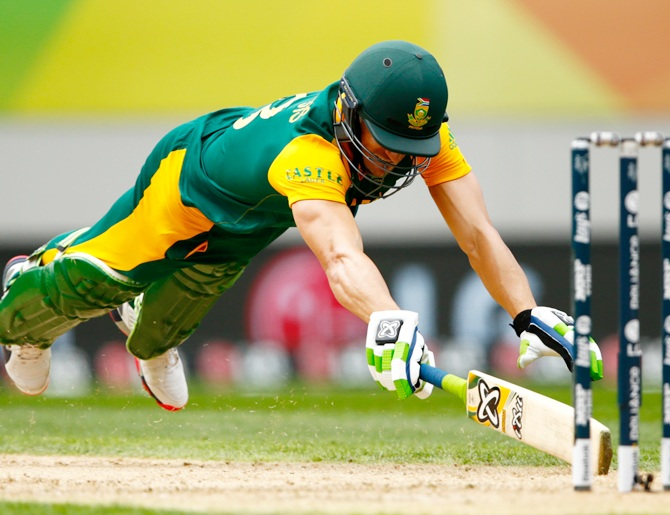 Faf du Plessis dives to make his crease. Photograph: Phil Walter/Getty Images