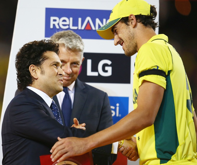 Mitchell Starc receives the Player of the Tournament medallion from Sachin Tendulkar. Photograph: Mark Kolbe/Getty Images
