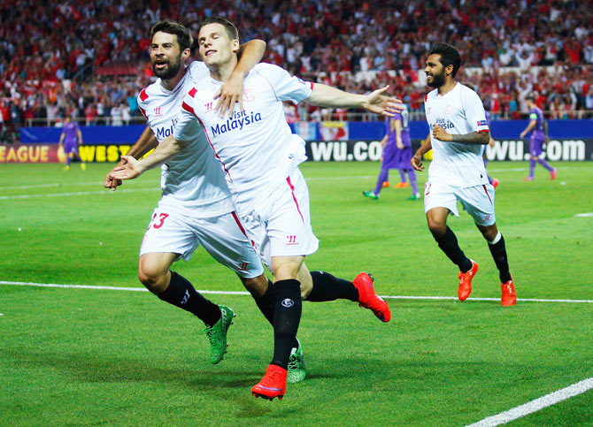 Kevin Gameiro of Sevilla celebrates scoring his team's third goal with teammate Coke during their UEFA Europa League first leg semi-final against ACF Fiorentina at Estadio Ramon Sanchez Pizjuan in Seville on Thursday