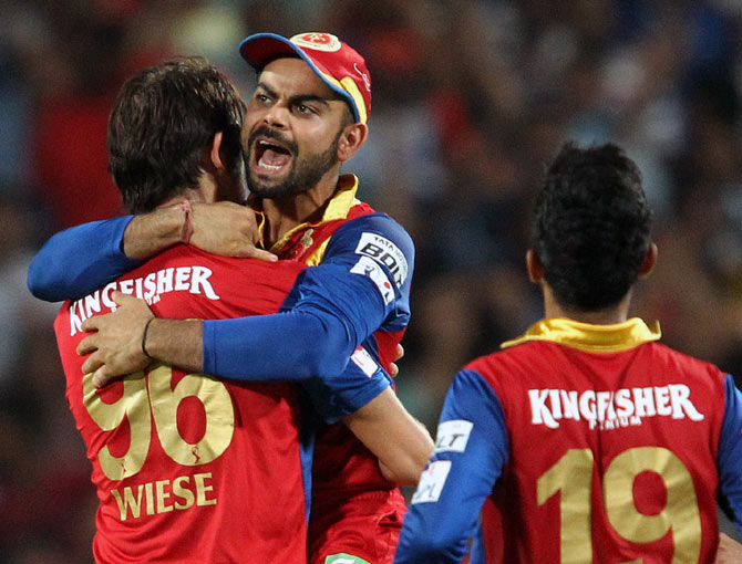 Royal Challengers Bangalore captain Virat Kohli congratulates David Wiese  after he claimed the wicket of Steven Smith.