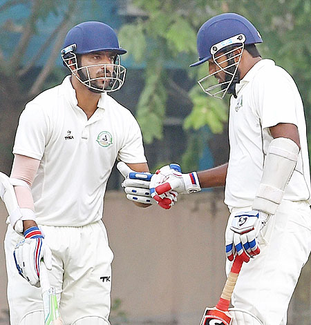Vidarbha's Wasim Jaffer (right) celebrate his 10000 runs in Ranji Trophy cricket with teammate Faiz Yakub Fazal during their Ranji Trophy match against Bengal at Jadavpur University campus in Kolkata on Sunday