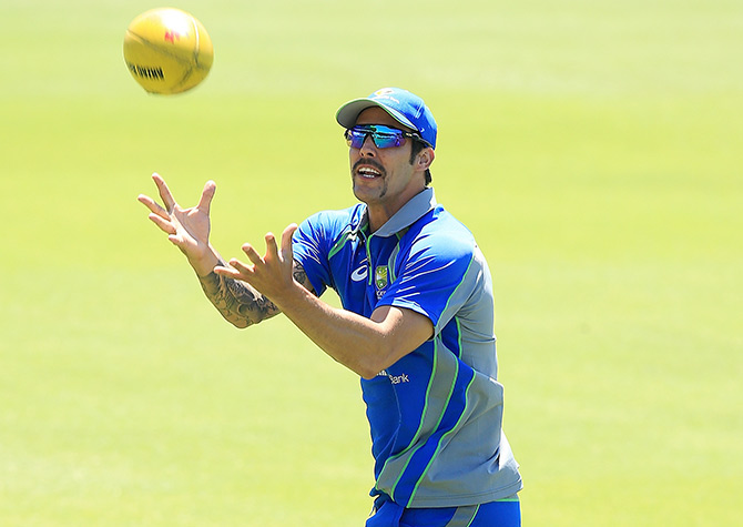 Mitchell Johnson marks a football as players warm up during an Australian nets session