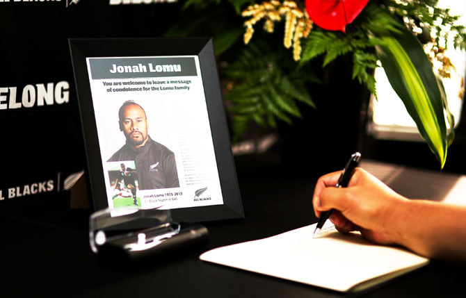 A well-wisher signs a condolence book at New Zealand Rugby Union headquarters following All Black legend Jonah Lomu's death in Wellington on Wednesday