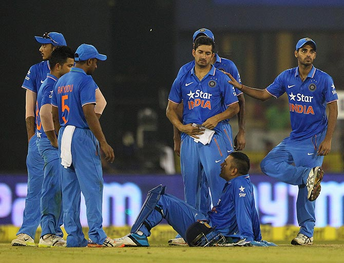 Indian players look on as play is suepended due to the crowd throwing bottles onto the pitch during the second T20 International in Cuttack