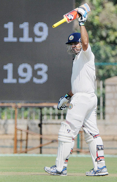 Virender Sehwag celebrating raises his bat after scoring a century in Ranaji Trophy against Karnataka in Mysore on Thursday