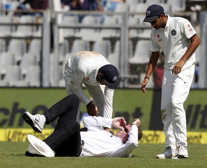 Rediff Sports - Cricket, Indian hockey, Tennis, Football, Chess, Golf - Umpire Reiffel leaves the field after being hit by ball