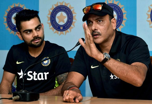 Virat Kohli (left) looks on as Indian Team Director Ravi Shastri addresses the media