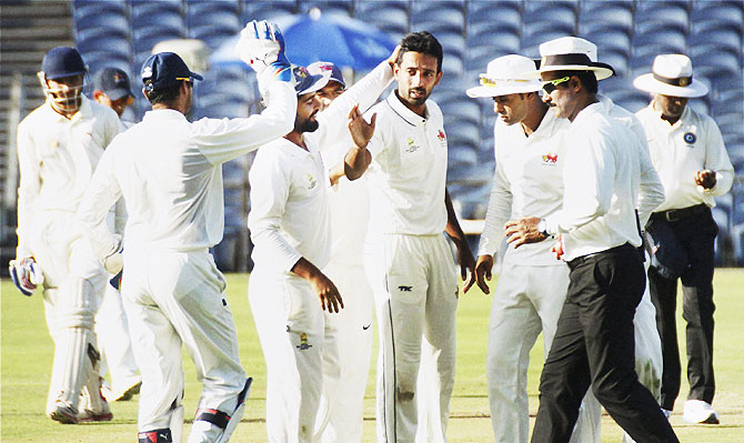 Dhawal Kulkarni is congratulated by his Mumbai teammates after claiming four wickets on the opening day of the Ranji Trophy final against Saurashtra