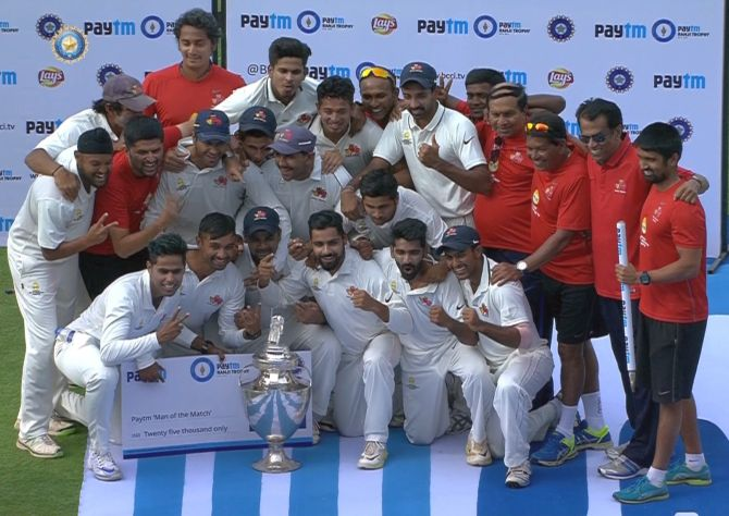 The triumphant Mumbai team poses with the Ranji Trophy after beating Saurashtra by an innings and 21 runs in the final in Pune