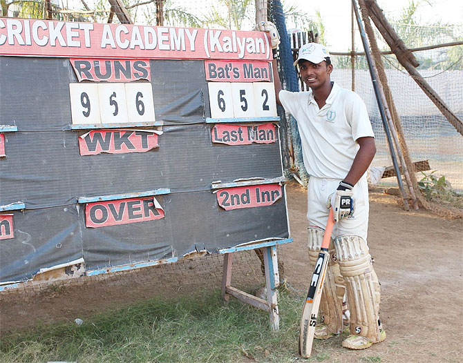 Pranav Dhanawade stands proudly beside the scoreboard at the end of Day 1