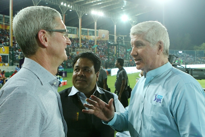 Alan Wilkins, right, speaks with Apple CEO Tim Cook, left, as IPL Chairman Rajeev Shukla looks on at an IPL game in 2016