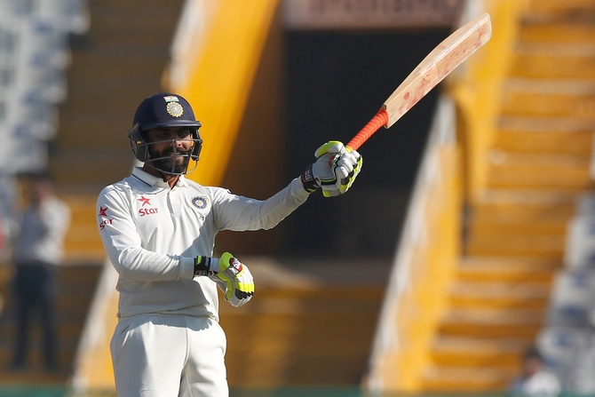 Ravindra Jadeja celebrates his half century, swirling his bat like a sword