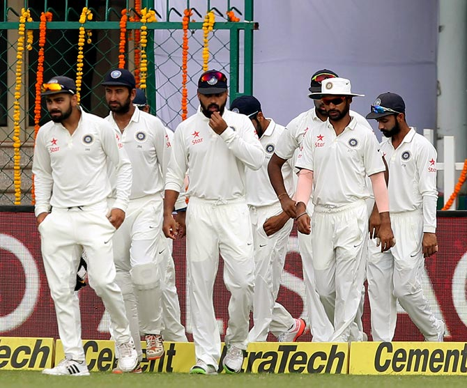 India captain Virat Kohli (left) leads his team out on to the field