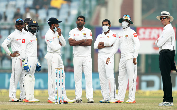 Face mask-donning Sri Lankan players wait for a DRS review on Day 4 of the 3rd Test in New Delhi on Tuesday