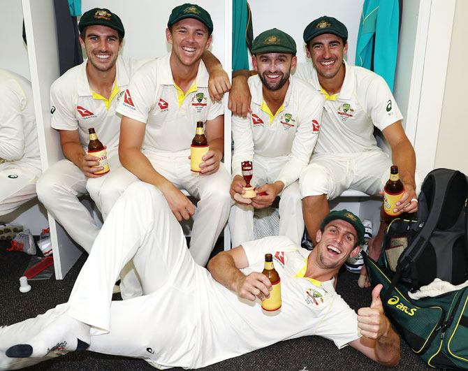 Australia bowlers Pat Cummins, Josh Hazlewood, Nathan Lyon Mitchell Starc and Mitch Marsh celebrate in the changerooms after the team's Ashes win over England at WACA in Perth on Monday
