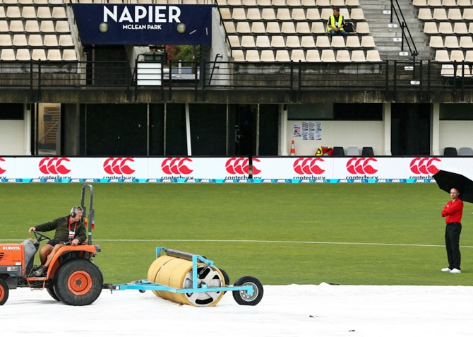 Ground staff tend to the covers prior to the second One-day International between New Zealand and Australia at McLean Park in Napier, New Zealand