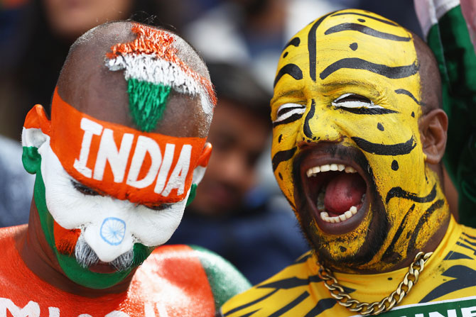 An Indian fan and his Bangladeshi counterpart enjoy a light moment as they watch the proceedings together