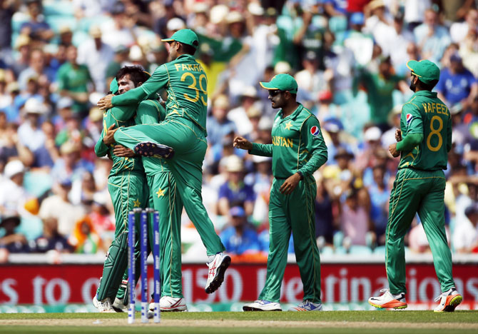 Pakistan's Mohammad Amir celebrates with team mates after dismissing India's Shikhar Dhawan
