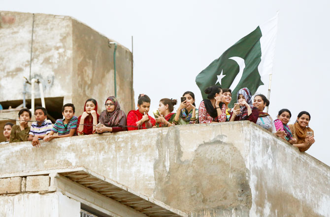 Women and children gather on a roof as they watch Sarfraz Ahmed's homecoming in Karachi on Tuesday