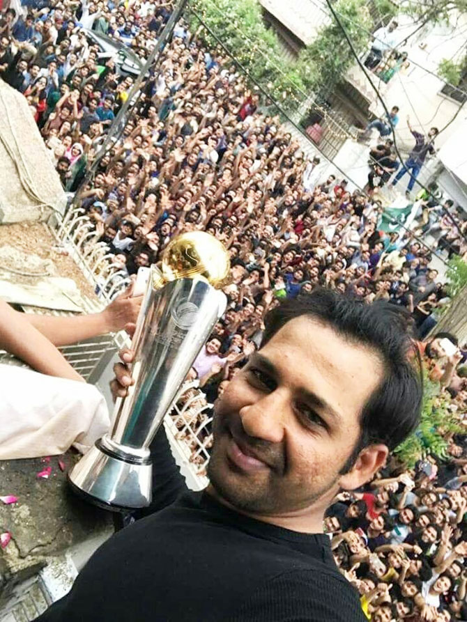 Pakistan captain Sarfraz Ahmed's home is surrounded by fans as he shows off the Champions Trophy from the balcony of his home
