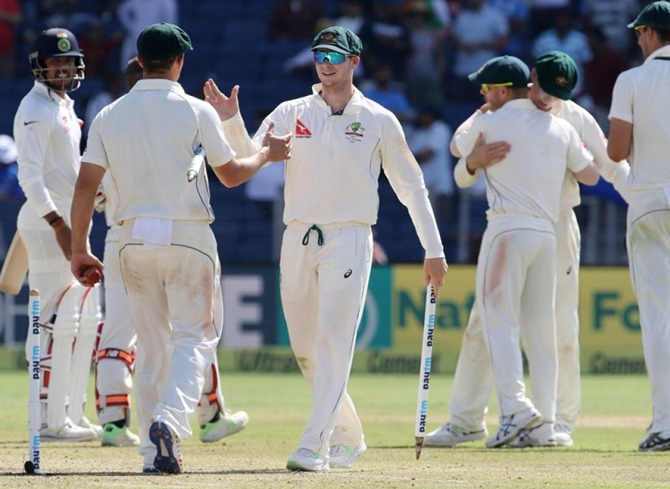 Australian players celebrate after winning the first Test match in Pune on March 1