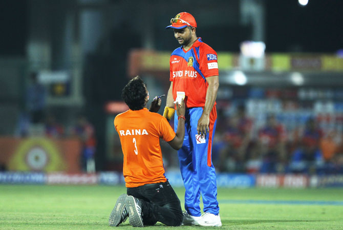 A spectator breaks the security cordon, runs on to the field to ask Gujarat Lions captain Suresh Raina for an autograph
