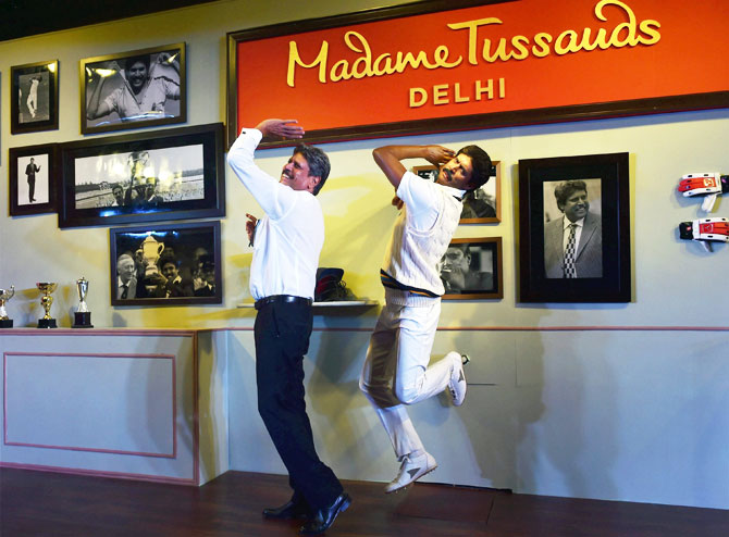 Former Indian Cricket Caption Kapil Dev poses with a wax figure of himself after unveiling the statue at Madame Tussauds Delhi, in New Delhi on Thursday